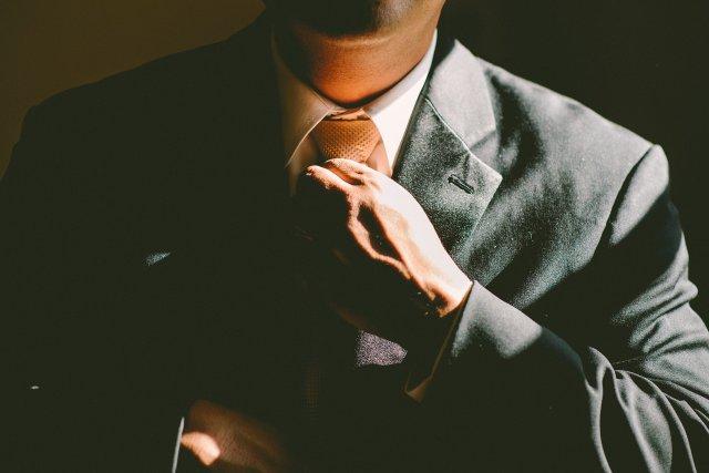 ネクタイを締める黒スーツ