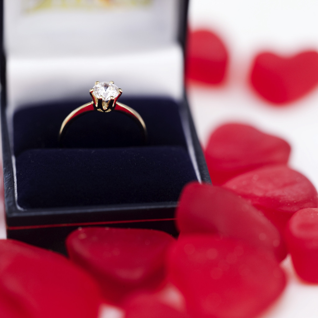 Red Heart Shaped Candies Surrounding an Engagement Ring in a Box
